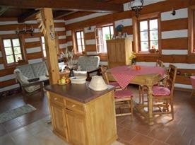 Společenská místnost s pohovkou, křesly, stolkem a jídelním koutem