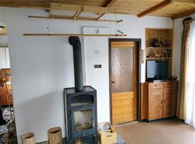 Společenská místnost s krbovými kamny a televizí