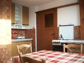 Kuchyně s linkou, sporákem, lednicí a jídelním koutem