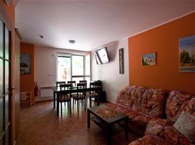 Obývací pokoj s rohovou sedačkou, stolem a židlemi