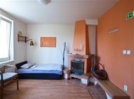 Ložnice s lůžky, sedačkou, stolkem, krbem a televizí