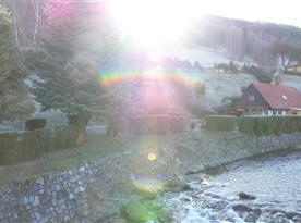 Zalitá zahrada sluncem a tekoucí horskou říčkou Bělou