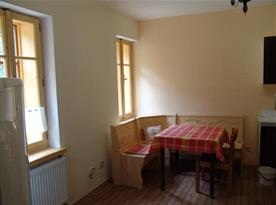 Pokoj A s kuchyňkou, lednicí, rohovou lavicí, stolem a židlí