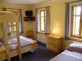 Pokoj B s lůžky, patrovou postelí, komodou a televizí