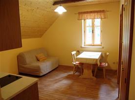Pokoj D s rozkládacím gaučem, stolem, židlemi a kuchyňkou