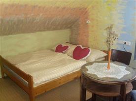 Podkrovní ložnice B s lůžky, skříní, stolkem a židlí