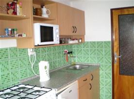 Kuchyně se sporákem, ledničkou, varnou konvicí, kávovarem a mikrovlnnou troubou