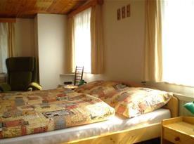 Ložnice A s lůžky, skříní, nočním stolkem, lampičkou a křeslem