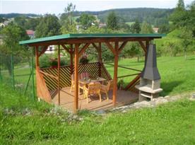 Zastřešené venkovní posezení sena zahradním nábytkem u krbu