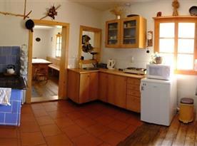 Kuchyně s rychlovarnou konvicí, lednicí, mikrovlnkou a kachlovými kamny