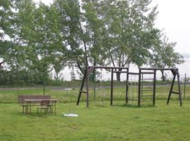 Dětské hřiště v areálu kempu v pozadí s vodní nádrží