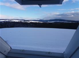 Pohled z podkroví na zimní krajinu