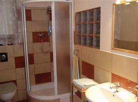 Koupelna se sprchovým koutem, toaletou, umývadlem a zrcadlem