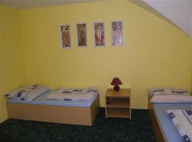 Pokoj B s lůžky, nočním stolkem a lampičkou