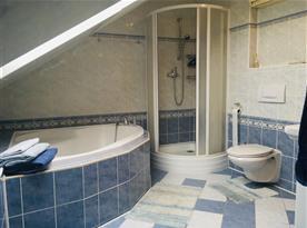 Koupelna s toaletou, vanou a sprchou v rámci podkrovního pokoje v hlavní budově