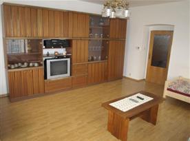 Pokoj s lůžky, obývací stěnou a televizí