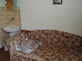 Pokoj v přízemí se sedačkou a umývadlem