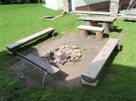 Venkovní ohniště s posezením u chaty