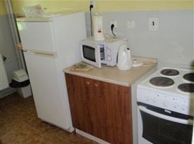 Společná kuchyně v 1. patře se sporákem, lednicí, mikrovlnou troubou a varnou konvicí