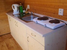 Kuchyňský kout v podkroví s dvouplotýnkovým vařičem a rychlovarnou konvicí