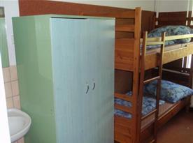 Pokoj v přízemí s patrovou postelí, skříní a umývadlem