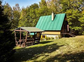 Zadní pohled na chatu se zastřešeným posezením
