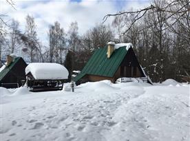 Chata v zimě s venkovním posezením