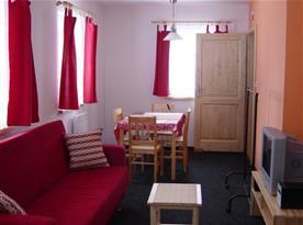 Obývací pokoj se sedačkou, televizí a jídelním koutem
