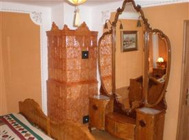 Ložnice se starožitným nábytkem a kachlovými kamny