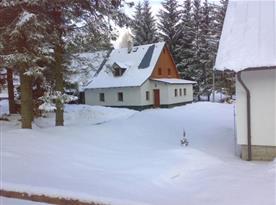 Pohled na chatu v zimě od příjezdové cesty