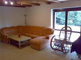 Obývací pokoj s rohovou sedačkou, houpacím křeslem a výhledem do zahrady