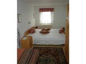 Pohled na pokoj s manželským lůžkem