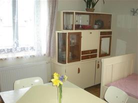 Pohled na kuchyň se sekretářem, jídelním stolem a židlemi