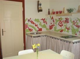 Pracovní deska v kuchyni s dřezem a kuchyňským stolem s židlemi