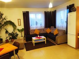 Společenská místnost s kuchyňským koutem, jídelním koutem a obývací částí s TV.