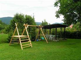 Udržovaná zahrada s houpačkou a zastřešeným posezením