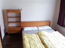 Pokoj s manželskou postelí a dětskou postýlkou