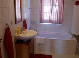 Koupelna s vanou, umyvadlem a zrcadlem