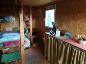Společenská místnost s rozkládacím gaučem a kuchyňským koutem