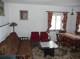 Pohled na společenskou místnost s jídelním stolem a pohovkou