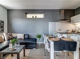 Pohled na společenskou místnost s jídelním koutem a sedací soupravou s televizorem