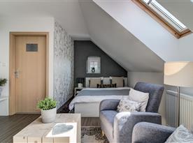 Pohled na pokoj v podkroví s manželským lůžkem a relaxačním koutkem