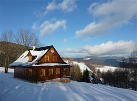 Chata zapadaná sněhem v blízkosti lyžařských vleků
