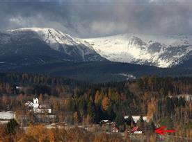 Chata vpravo dole se zasněženými vrcholky Krkonoš v pozadí