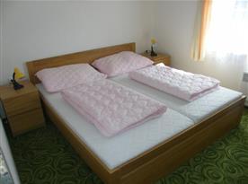 Ložnice s lůžky, nočními stolky a lampičkami v přízemí