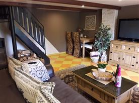 Obývací pokoj s jídelním koutem, krbem a schody do patra