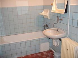 Koupelna s vanou, umyvadlem a toaletou v apartmánu A