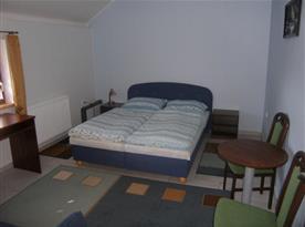 Modrý pokoj s lůžky výhledem na venkovní posezení