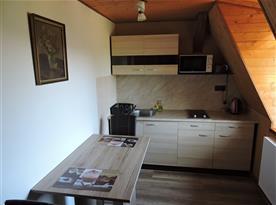 Kuchyň s varnou deskou, mikrovlnnou troubou a jídelním stolem