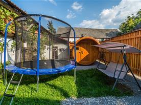 Zahrada s koupacím sudem, trampolínou a saunou